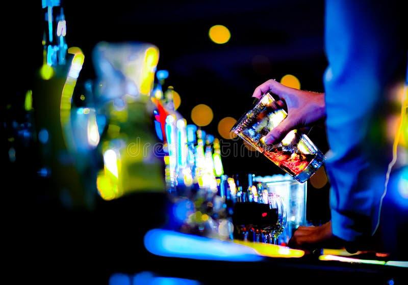 O barman que faz o cocktail do álcool no contador da barra no clube noturno, empregado de bar está fazendo o cocktail imagens de stock royalty free