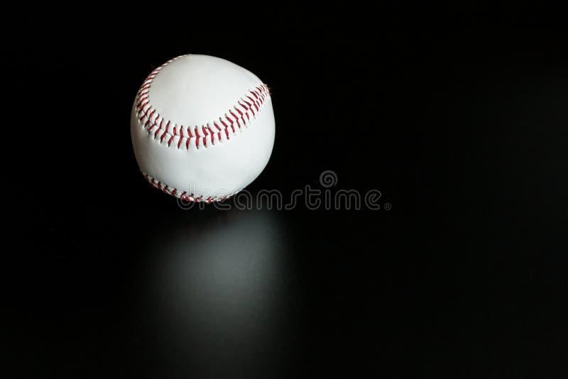 O basebol branco com vermelho emenda a bola de couro no fundo preto foto de stock