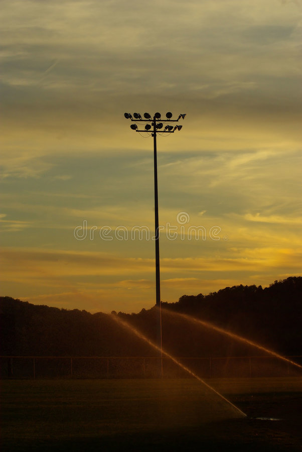 O basebol ilumina molhar do campo foto de stock