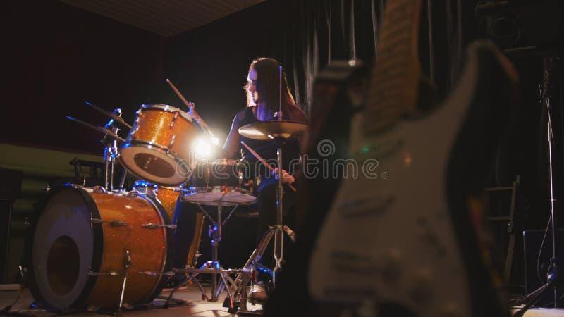O baterista da menina, jovem mulher atrativa joga os cilindros fotos de stock royalty free