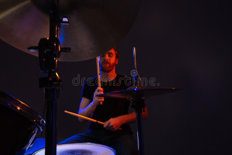 O baterista farpado atrativo do homem com olhos fechados que aprecia o jogo rufa fotos de stock