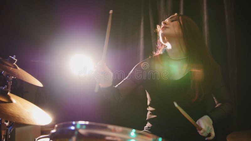 O baterista gótico da percussão da menina executa a música divide - a música rock adolescente fotografia de stock