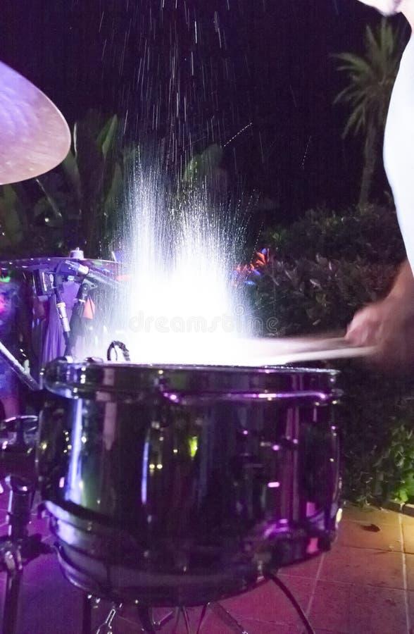 O baterista que bate e que espirra cilindros na noite mostra imagem de stock