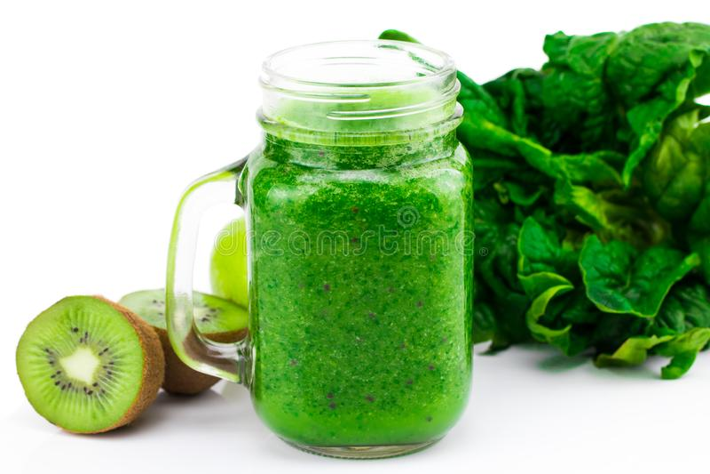 O batido verde saudável com espinafres e o quivi em um frasco agridem o isolat foto de stock