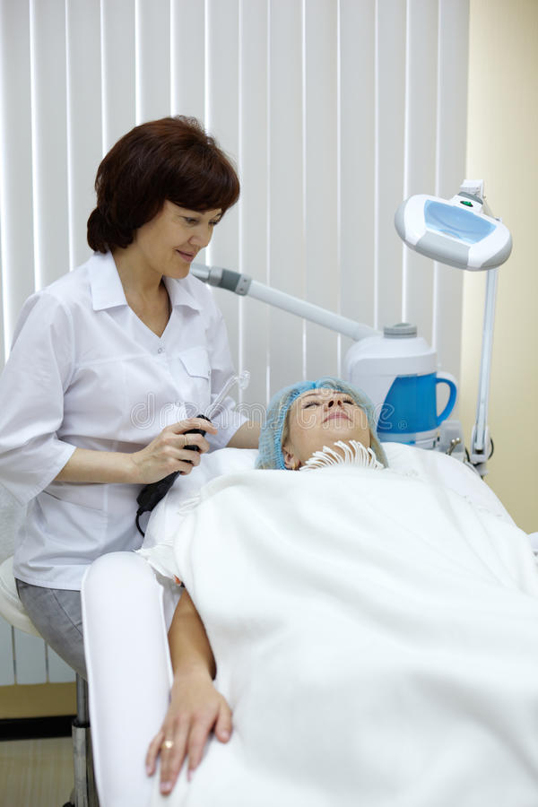 O Beautician conduz uma sessão do tratamento da pele. imagem de stock