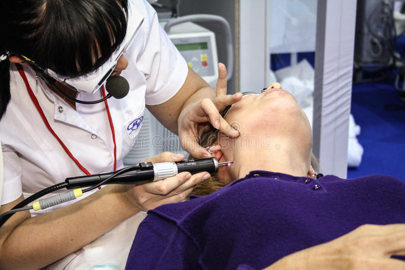 O Beautician executa um procedimento do laser fotografia de stock royalty free
