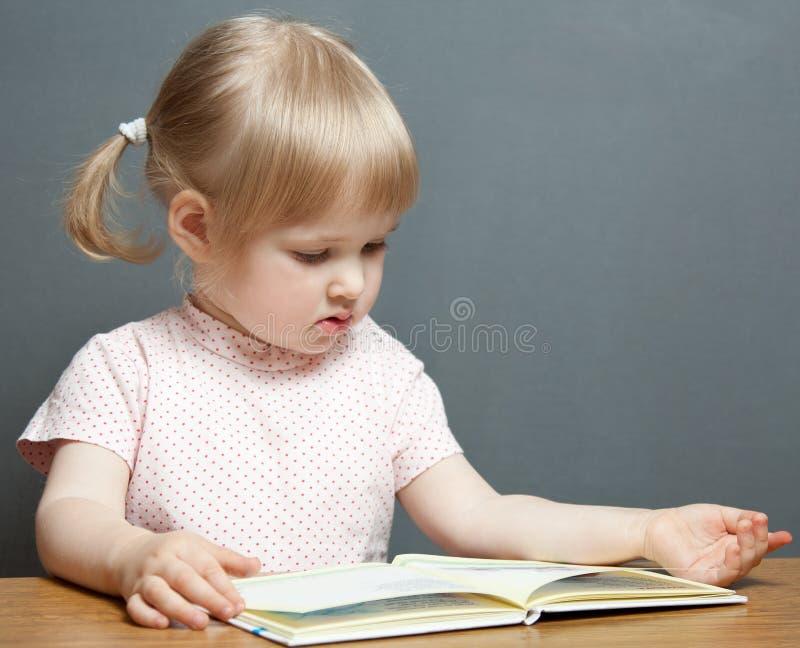 O bebé está lendo o livro fotos de stock