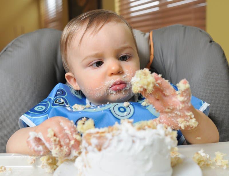 O bebé faz o mess do bolo fotos de stock royalty free