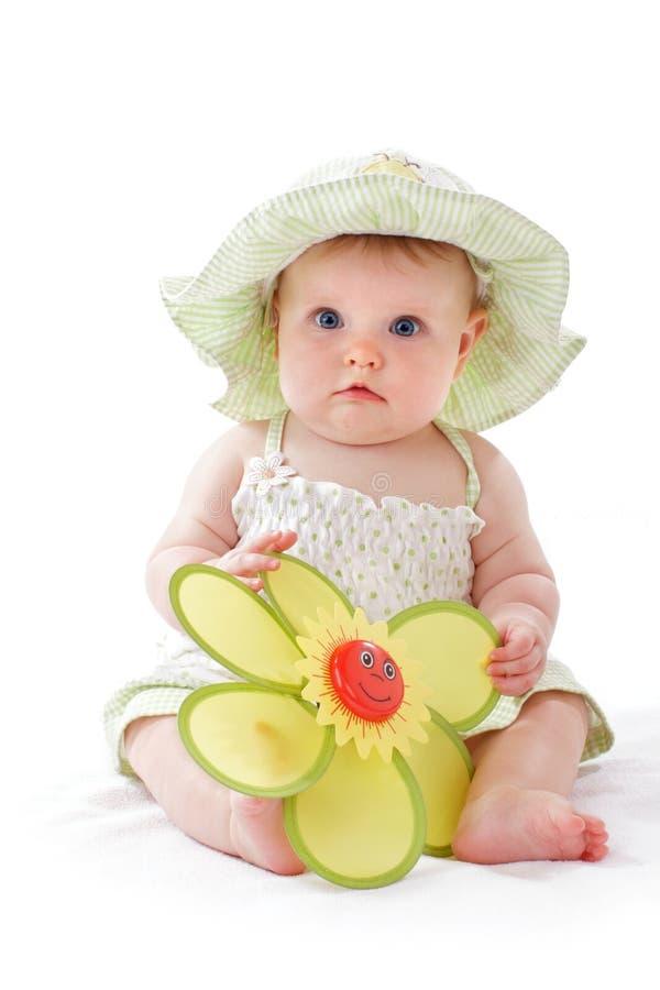 O bebé no chapéu bonito joga com flor do brinquedo fotografia de stock