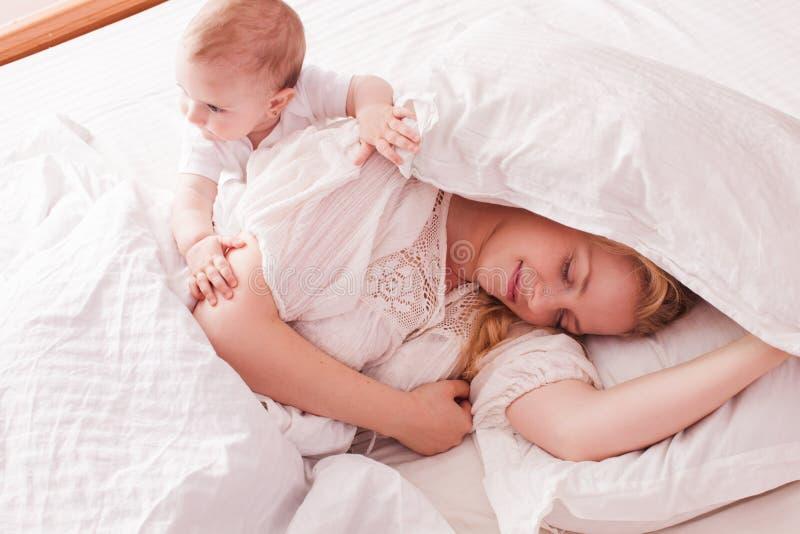 O bebê acorda a mamã sonolento fotos de stock royalty free