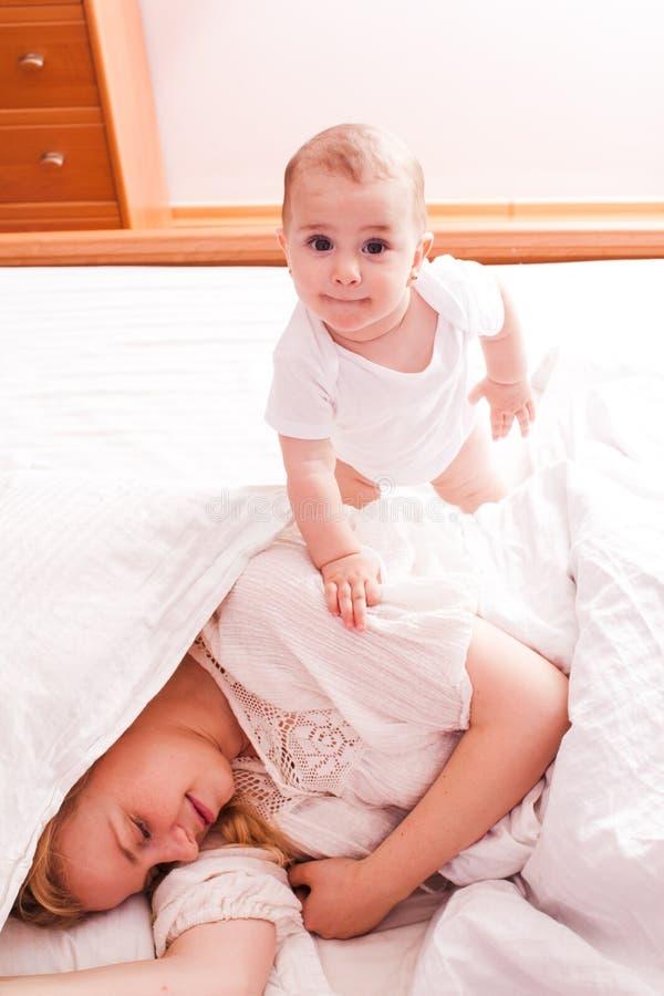 O bebê acorda a mamã sonolento imagem de stock