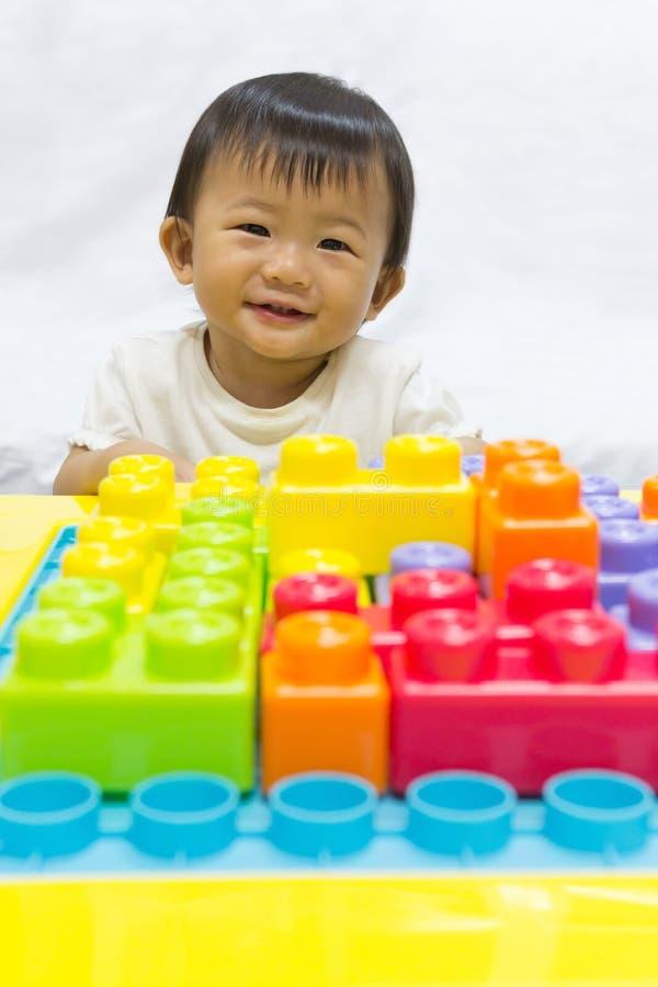 O bebê adorável asiático um ano está apreciando o brinquedo da serra de vaivém para a criança fotos de stock royalty free