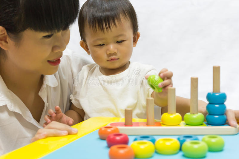O bebê adorável asiático um ano está jogando a pirâmide do enigma da cor para fotografia de stock
