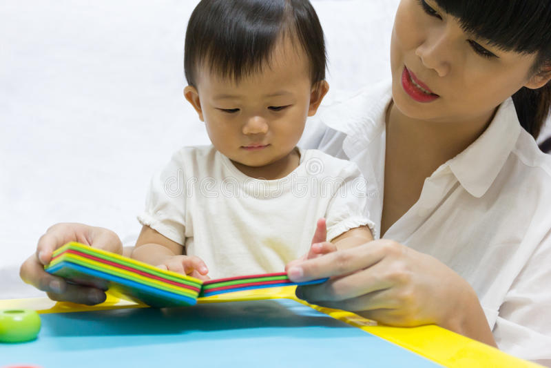 O bebê adorável asiático um ano está olhando o livro para a criança imagens de stock royalty free