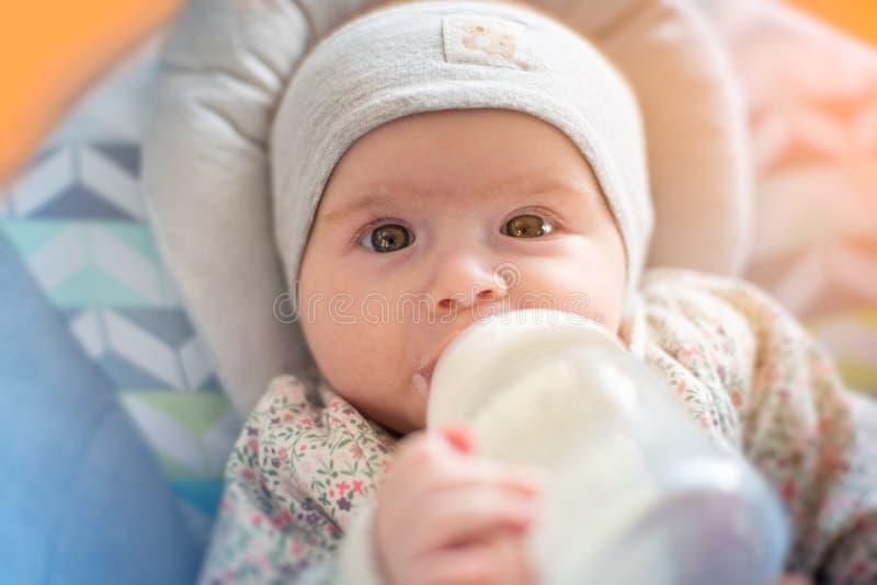 O bebê adorável bebe o leite da fórmula da garrafa imagem de stock