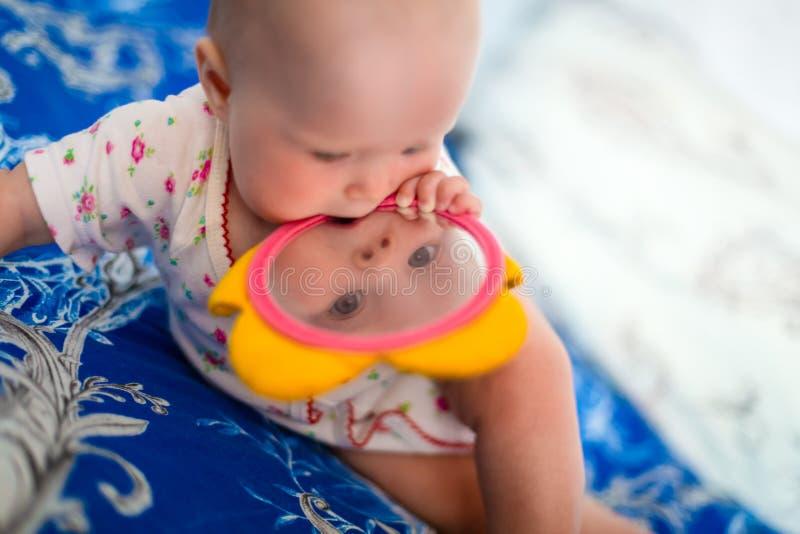 O bebê adorável e bonito senta-se na cama e nos jogos com brinquedos que é espelho das crianças A criança pequena está guardando  imagem de stock