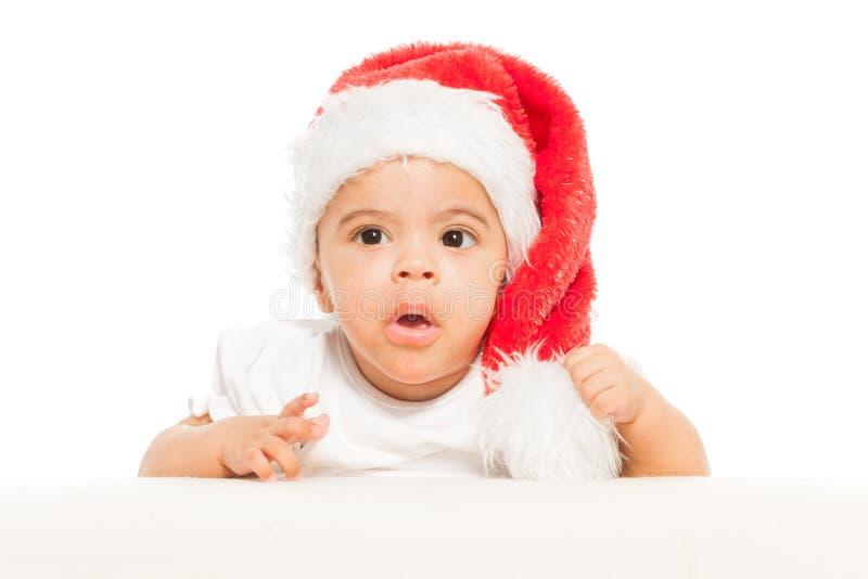 O bebê africano no chapéu vermelho do Natal olha surpreendido imagem de stock royalty free
