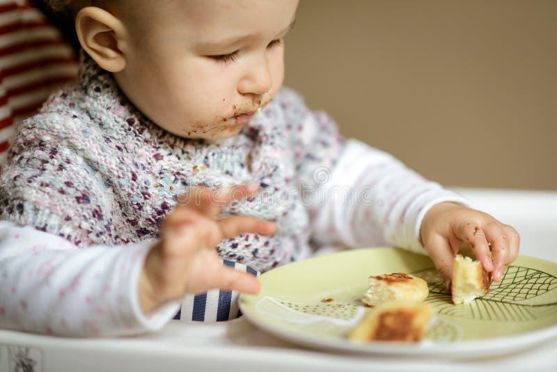 O bebê agradável com cara desarrumado que come o queijo endurece imagem de stock