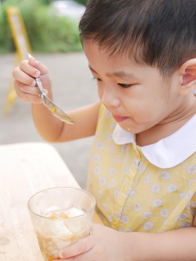 O bebê asiático aprecia tentar o alimento novo só, ovos quentes imagens de stock