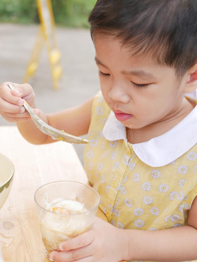 O bebê asiático aprecia tentar o alimento novo só, ovos quentes imagem de stock