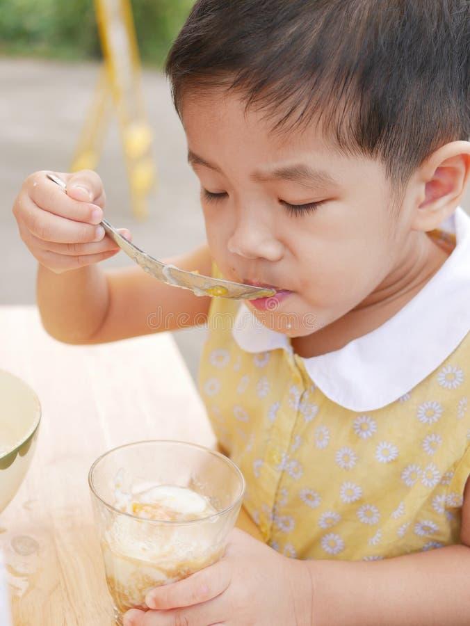 O bebê asiático aprecia tentar o alimento novo só, ovos quentes fotografia de stock