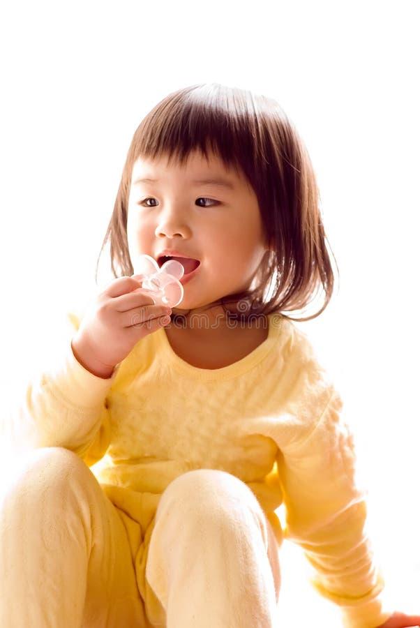 O bebê asiático encantador senta e suga o pacifier imagens de stock