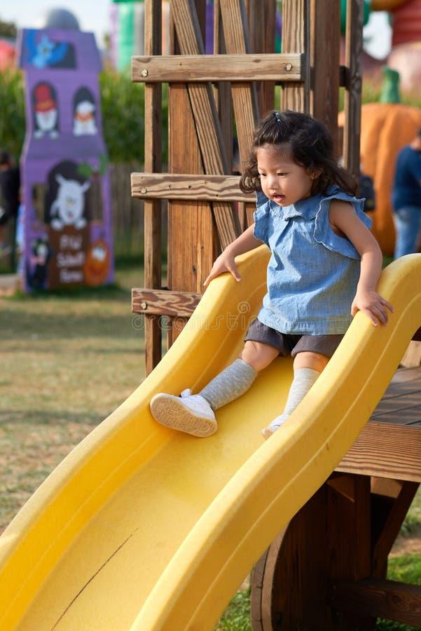 O bebê asiático está indo para baixo em uma corrediça no campo de jogos foto de stock royalty free