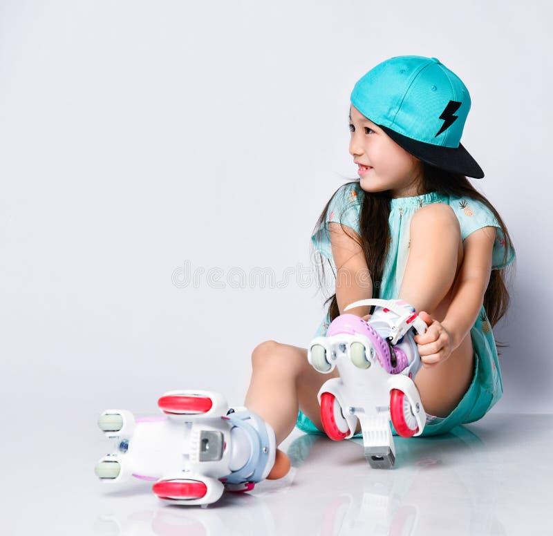O bebê asiático pequeno de sorriso feliz no tampão fresco do chapéu olha no lado que senta-se no assoalho e que põe sobre patins  fotos de stock royalty free
