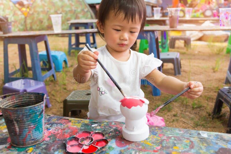 O bebê bonito asiático da menina está pintando colorido fotos de stock