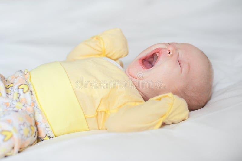 O bebê bonito boceja em um fundo branco imagens de stock royalty free