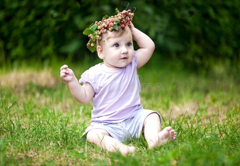 O bebê bonito com cabelo do ouro e o morango silvestre coroam fotografia de stock royalty free