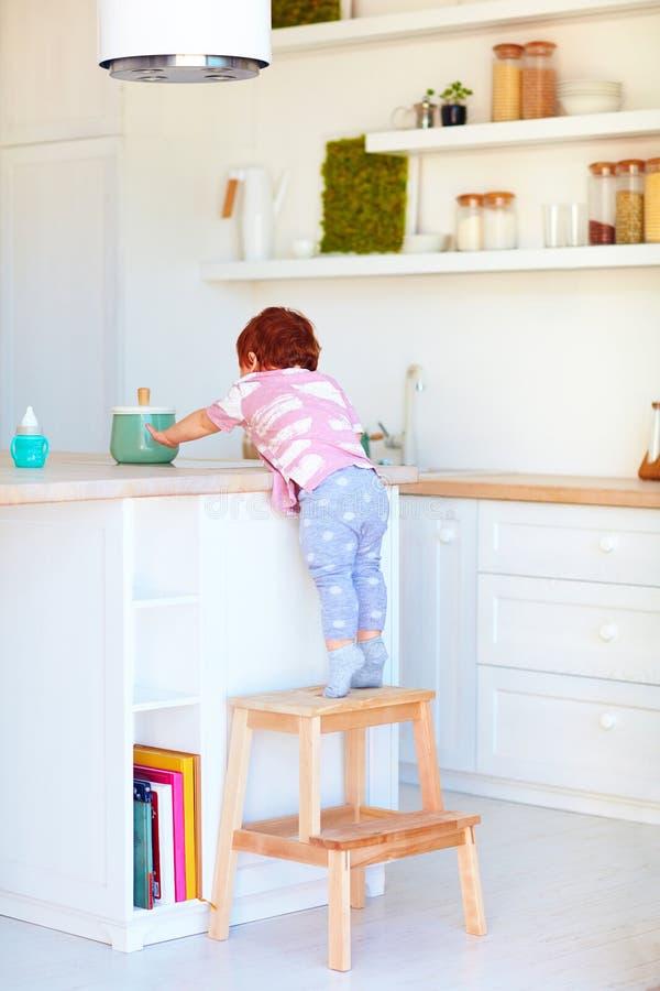 O bebê bonito da criança escala no tamborete da etapa, tentando alcançar coisas na mesa alta na cozinha fotografia de stock royalty free
