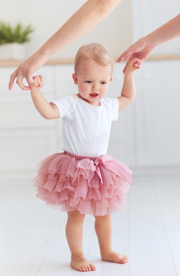 O bebê bonito da criança que faz suas primeiras etapas com ` s da mãe ajuda foto de stock