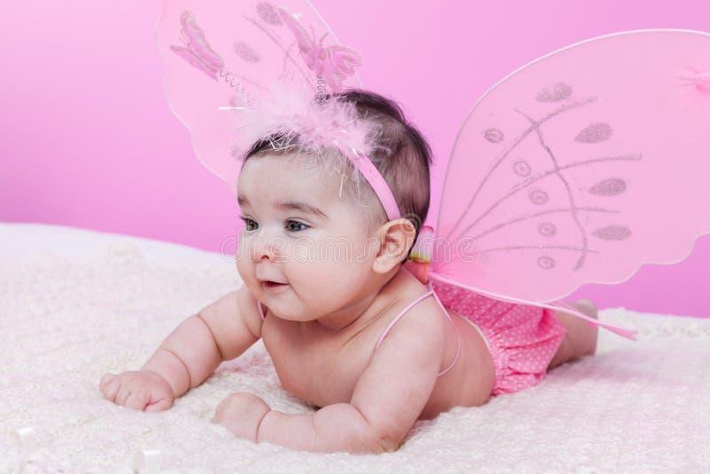 O bebê bonito, bonito, feliz, carnudo e sorrindo, com borboleta cor-de-rosa voa imagens de stock royalty free