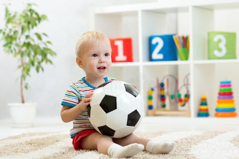 O bebê bonito joga com bola fotos de stock