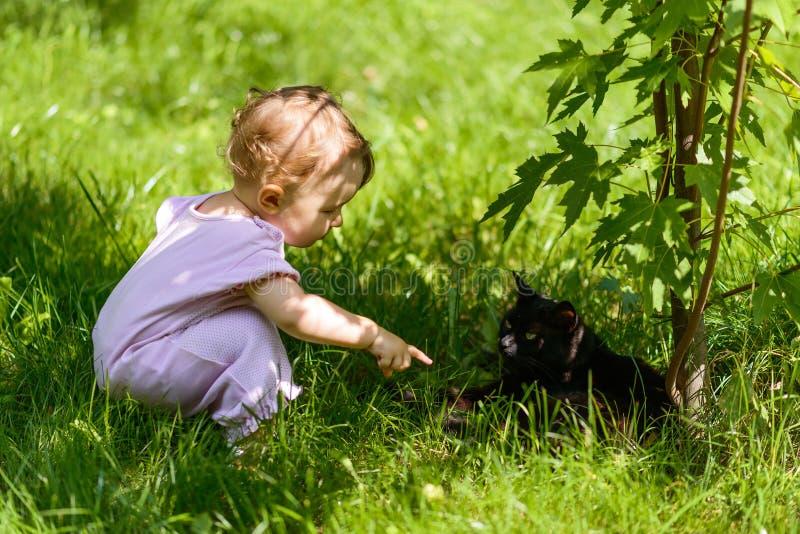 O bebê bonito joga com um gato preto no parque imagem de stock