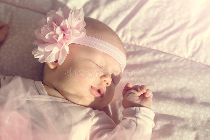 O bebê bonito pequeno encontra-se e dorme-se em sua cama, guardando o han imagens de stock royalty free