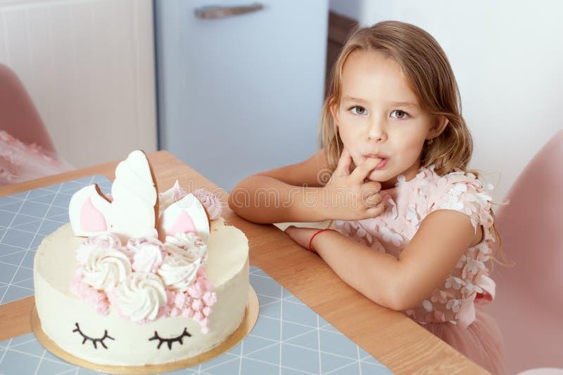 O bebê bonito prova um bolo de aniversário com um dedo fotos de stock