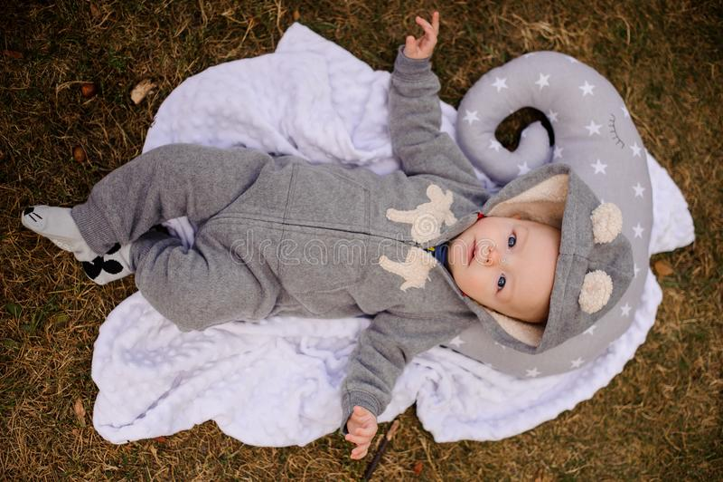 O bebê bonito vestiu-se no romper com a capa que encontra-se no descanso fotografia de stock royalty free