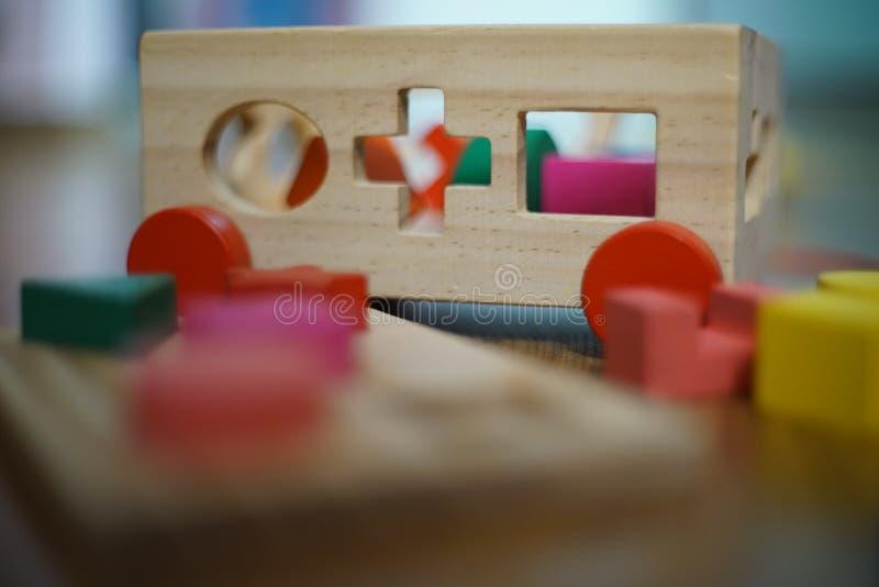 O bebê brinca os blocos de madeira do enigma foto de stock