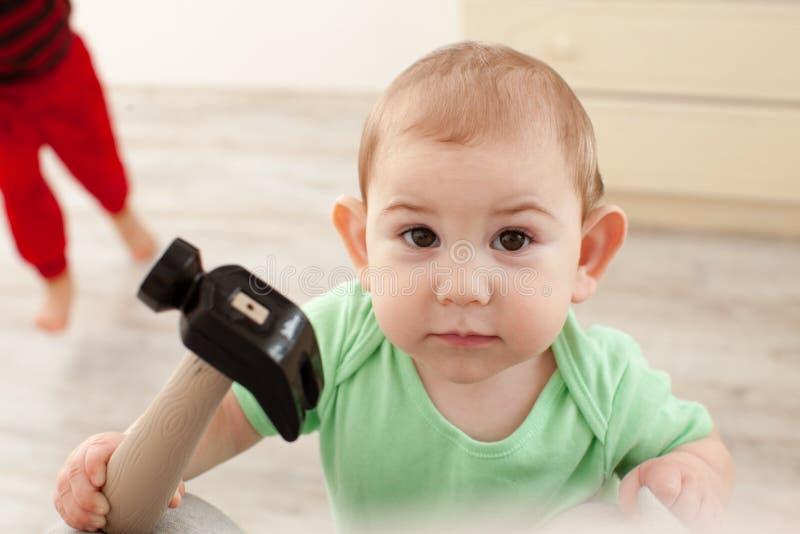 O bebê com martelo pretende trabalhar fotografia de stock