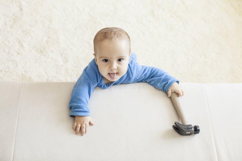 O bebê com martelo pretende trabalhar fotos de stock royalty free