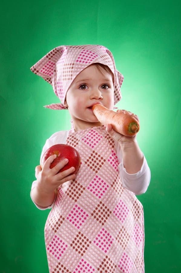 O bebê com um avental do lenço e da cozinha que mantém um vegetal isolado imagens de stock