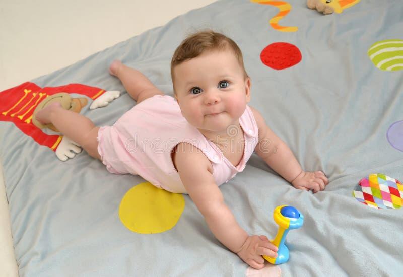 O bebê com um brinquedo encontra-se em um estômago em um tapete do jogo fotos de stock