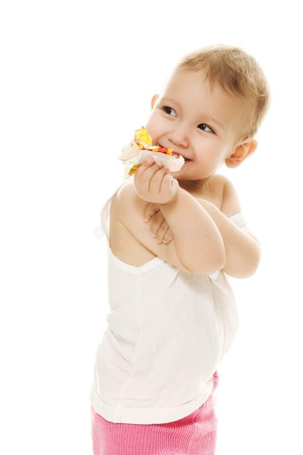 O bebê come doces em um fundo branco fotografia de stock royalty free