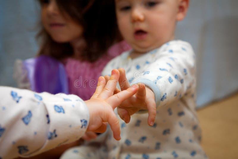 O bebê curioso põe três dedos sobre o espelho fotografia de stock royalty free
