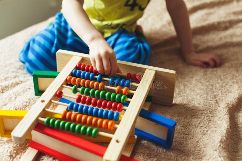 O bebê da criança em idade pré-escolar aprende contar Criança bonito que joga com brinquedo do ábaco Rapaz pequeno que tem o dive foto de stock