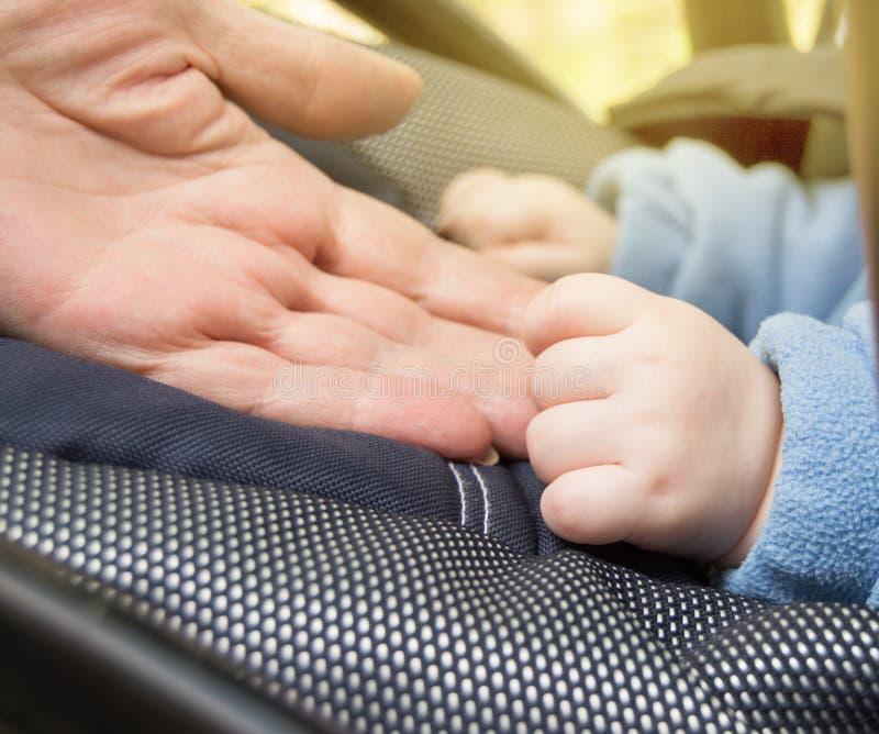 O bebê da mão e as mulheres idosas, avó, foco seletivo de foco seletivo, bebê estão no carrinho de criança ao andar fora, fim imagens de stock royalty free