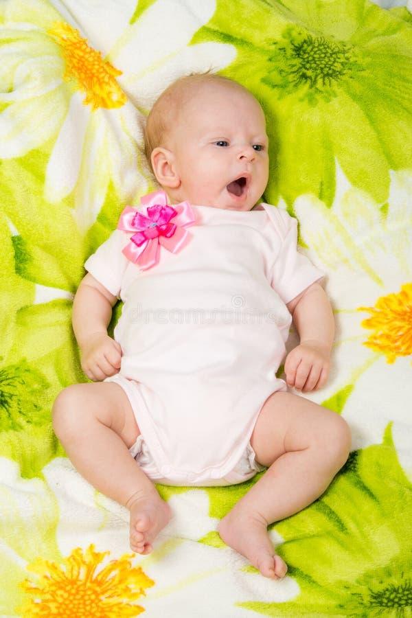 O bebê de dois meses boceja encontrando-se em sua parte traseira na cama foto de stock royalty free