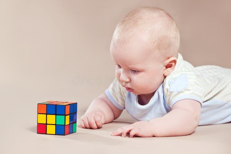 O bebê de sorriso está jogando com brinquedos imagens de stock
